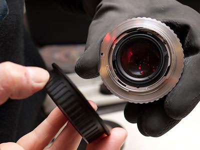 Take a pair of rubber kitchen gloves and hold the lens tightly as a whole. DO NOT grip the aperture ring with your thumb and fore finger as it is possible to permanently damage it, place the aperture to f8 to assure you do not damage it when twisting. Now get the plastic lens cap and tighten it onto the adapter until it clicks into place. The lens cap gives you excellent leverage and makes it far easier to fit the adapter into the right position.