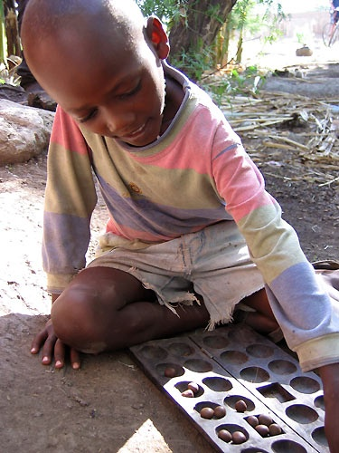 African child with game by Redbarron
