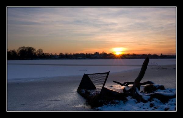 Sunset over frozen reservoir by Mrd06