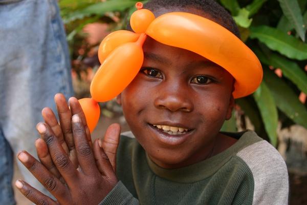 Street kid with an orange balloon by wicksy