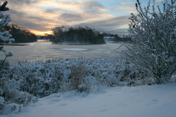 Sunrise over frozen lake by JohnMeik