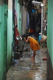 Girl washing her face in Kalighat alley, Kolkata, India