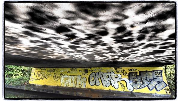 Camden under a bridge with water reflections by stevedigip