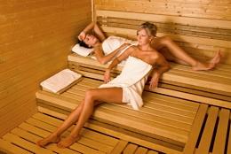 Sauna two healthy beautiful women relaxing lying wrapped in towel