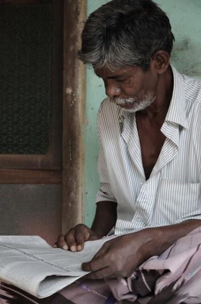 Kerala man reading newspaper by TRAVELLINGFOOTPRINT