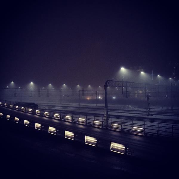 Railway station on a foggy night by olesyak