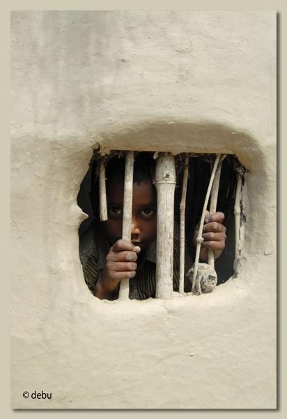 Boy looking through the window of a mud hut... by debu