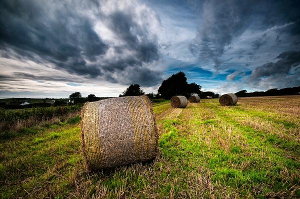 Hay bales under stormy sky. by ilocke