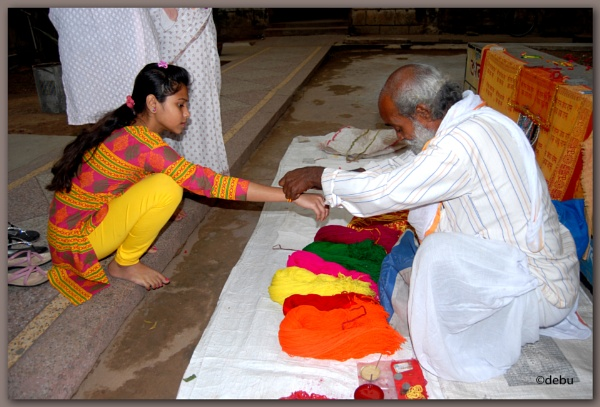 The tying of a symbolic thread around the wrist by Hindus... by debu