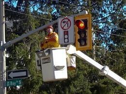 MAN AT WORK AT BAY and HERKIMER STREETS in HAMILTON placing new sign at TRAFFIC LIGHT