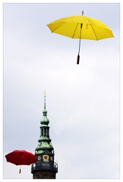 a steeple and a yellow and red umbrella
