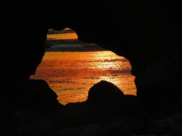 sunset through a  rock hole.