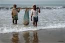Fishermen carrying fish by debu