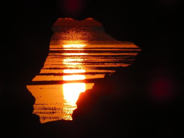 sunset  through a hole in a sea rock. by bulbulov