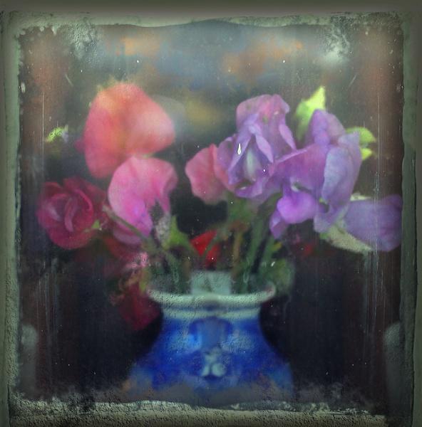 Cut flowers inside a dirty window by helenlinda