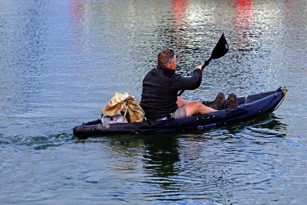 Man paddling dinghy tender - Lyme Regis harbour by starckimages