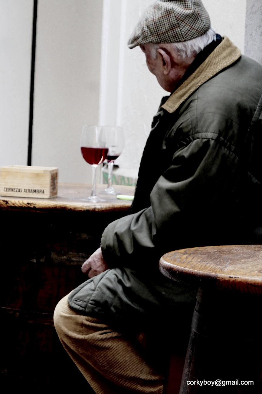 Man studies glass of wine.