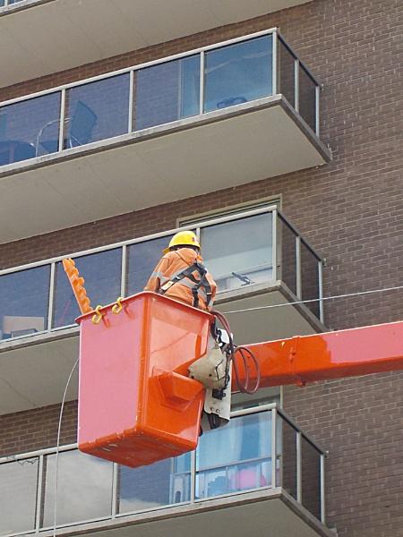 WORKER ON A CHERRY PICKER ON HERKIMER STREET by TimothyDMorton