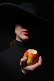 A Woman In A Black Hat holding bitten apple