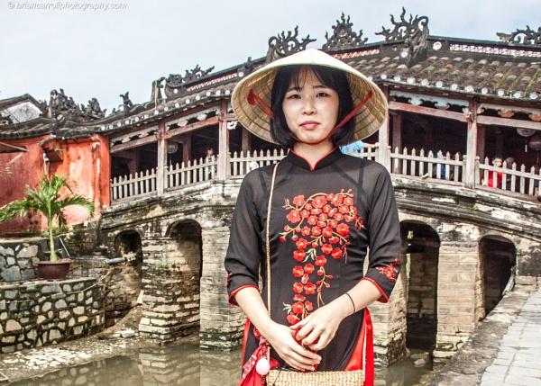 Vietnamese girl by the 16th century Pagoda footbridge, Hoi An, Vietnam by brian17302