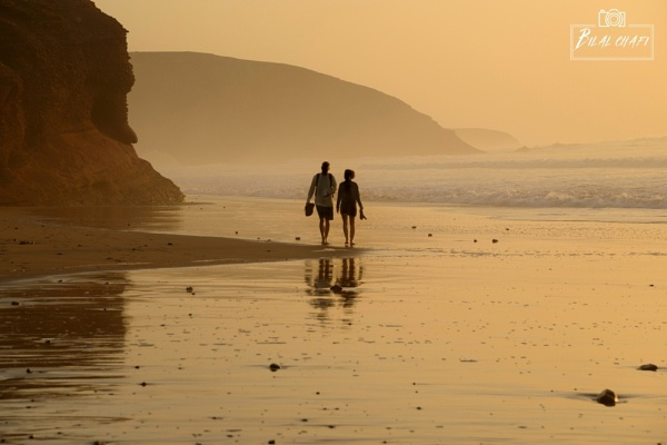 The lovely lone couple wandering at the beach amid sunset by chafibilal
