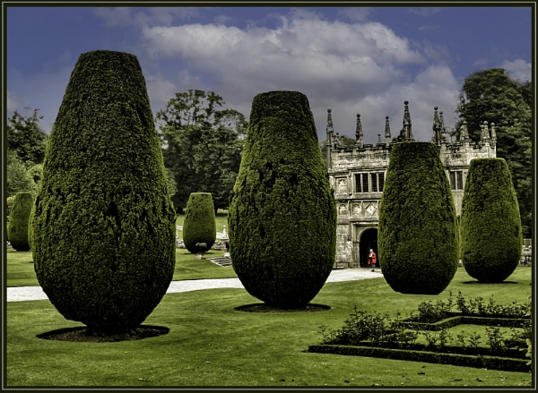 Manicured conifers and gatehouse at Lanydrock House by ivalyn