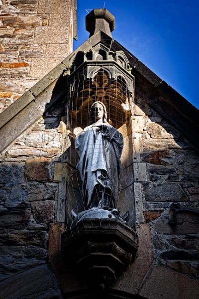 Statue on stone wall on church by rninov
