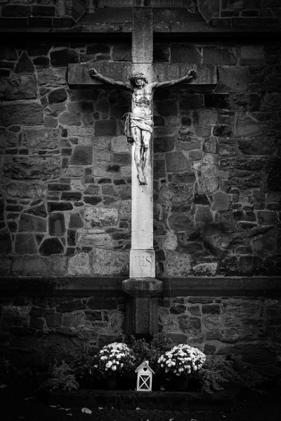 Stone cross and statue on the church wall by rninov